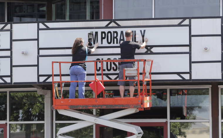 """Workers remove a sign saying """"Temporarily Closed"""" on the marquee at the Quarry Cinema in San Antonio on May 4."""