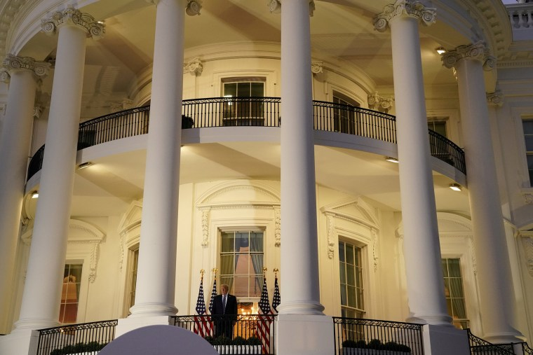 Image: President Donald Trump poses atop the Truman Balcony of the White House after taking off his mask as he returns from the Walter Reed Medical Center,