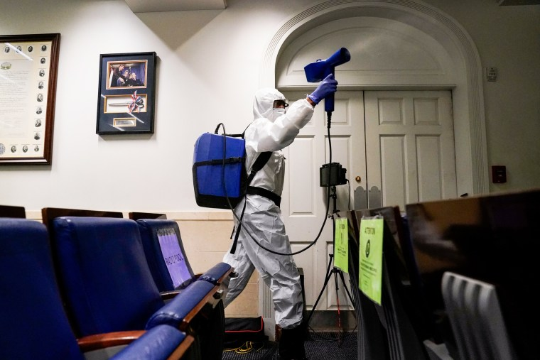 Image: A member of the White House cleaning staff sprays the press briefing room the evening of U.S. President Donald Trump's return from Walter Reed Medical Center