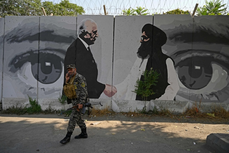 Image: A memnber of security personnel walks past a wall mural with images of U.S. Special Representative for Afghanistan Reconciliation Zalmay Khalilzad (L) and Taliban co-founder Mullah Abdul Ghani Baradar, in Kabul.