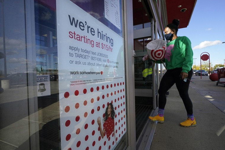 Image: A passerby walks past a hiring sign while entering a Target store in Westwood, Mass. Sept. 30, 2020.