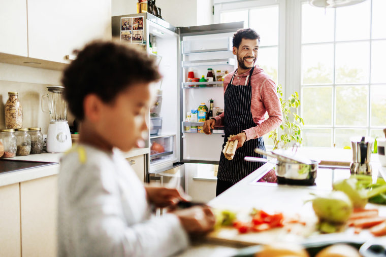 Image: Single Dad Smiling While He Prepares Lunch For Son At Home