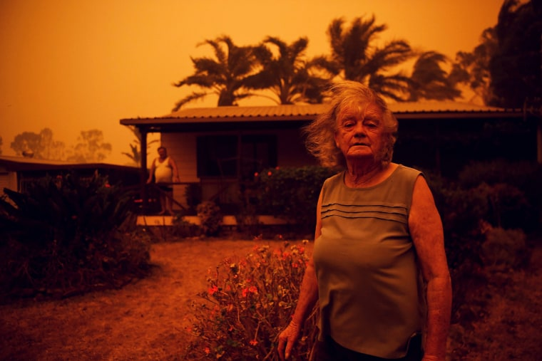 Image: Nancy Allen and Brian Allen stand outside the house as high winds push smoke and ash from the Currowan Fire towards Nowra, New South Wales, Australia