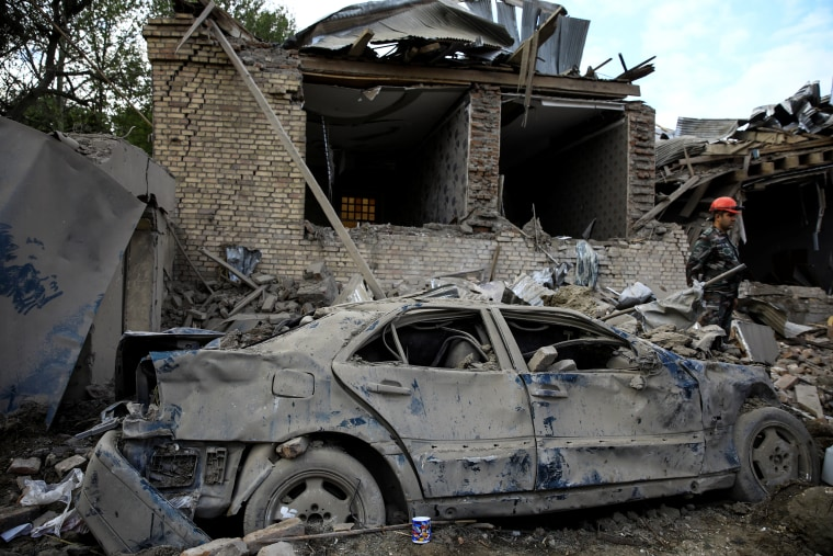 Image: A damaged car is seen at the blast site hit by a rocket during the fighting over the breakaway region of Nagorno-Karabakh in the city of Ganja