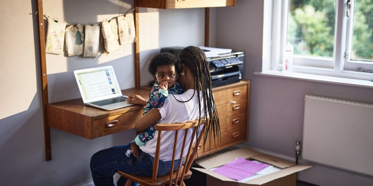 Mother with baby son working on laptop