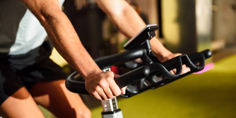 Midsection Of Man Using Exercise Bike