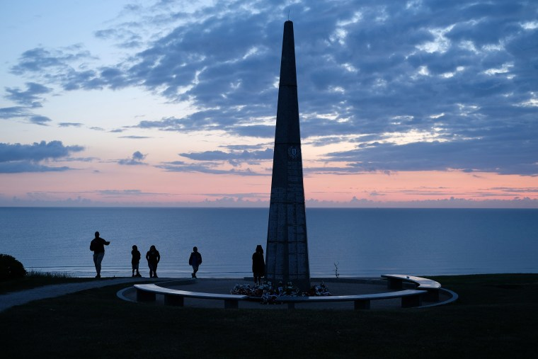 Image: Visitors walk up to the American 1st Infantry Division monument that overlooks Omaha Beach at sunrise on the 75th anniversary of the World War II Allied D-Day invasion