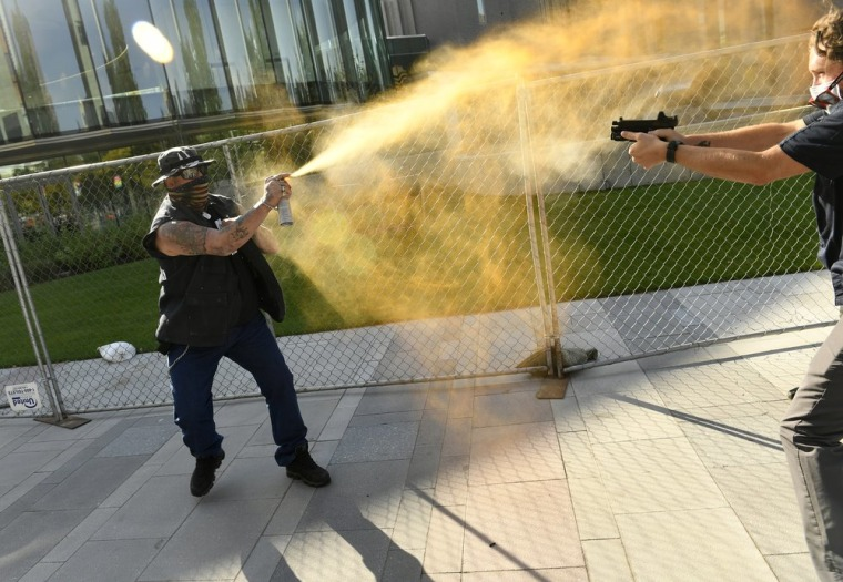 """A man sprays a chemical gas as another man fatally fires a gun Saturday in Denver. The man on the left, who was supporting the """"Patriot Rally,"""" sprayed at the man on the right. A private security guard working for a TV station was in custody."""