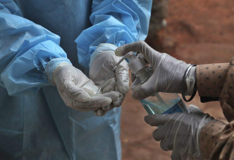 Image: A health worker cleans her hands with sanitizer