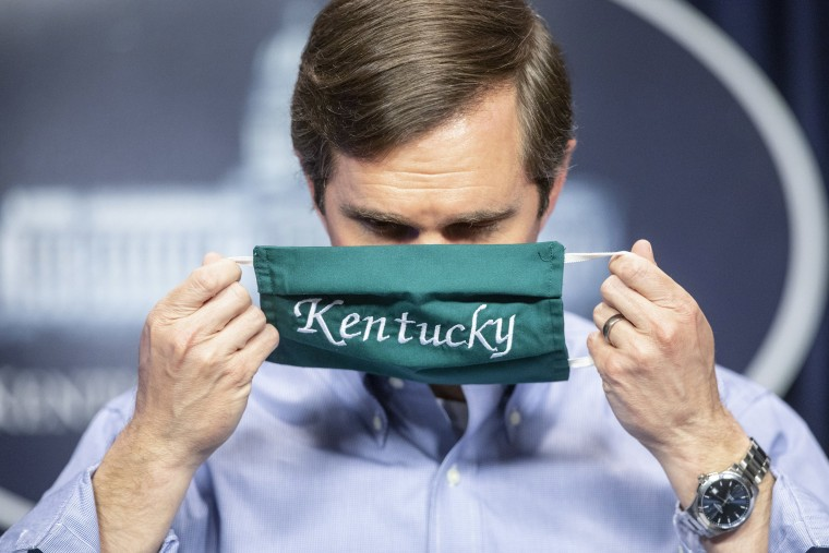 Image: Kentucky Gov. Andy Beshear puts on a face mask after speaking to reporters at the Capitol in Frankfort, Ky.