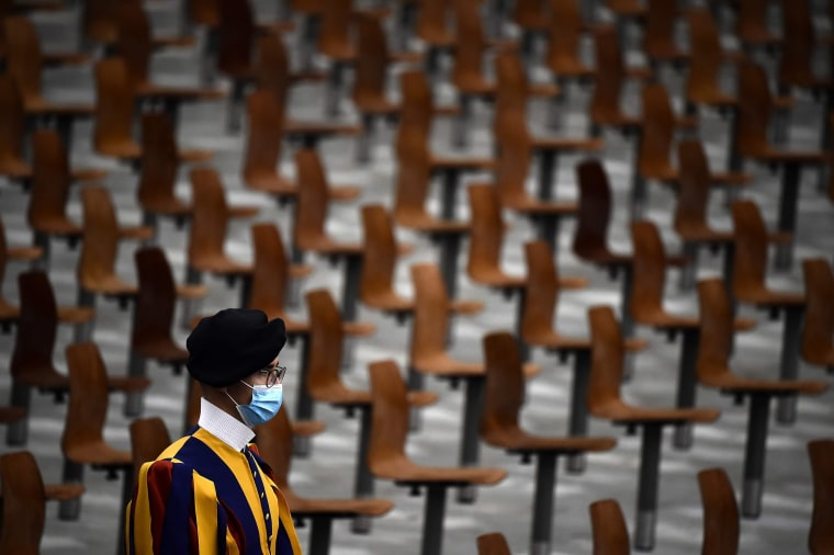 Image: A Swiss guard wearing a face mask stands in an almost empty Paul Vi Hall during Pope Francis  limited public audience at the Vatican