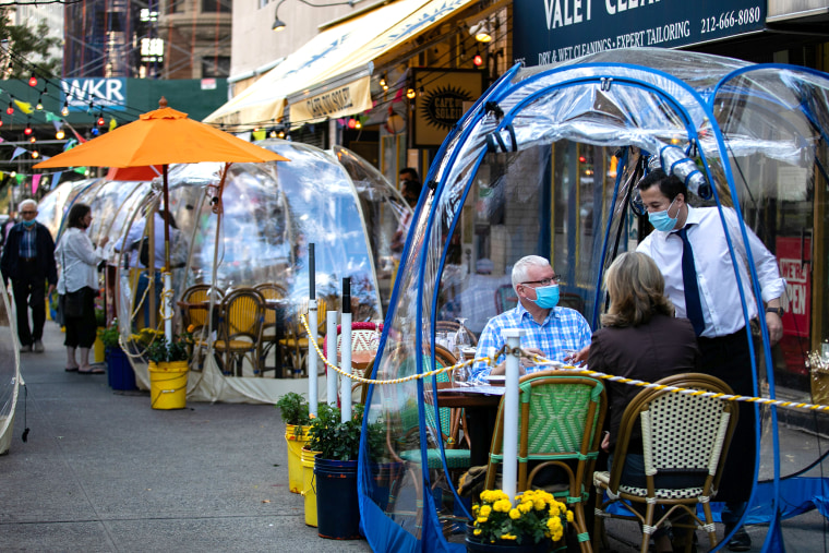 Image: People sit outside Cafe Du Soliel under bubble tents
