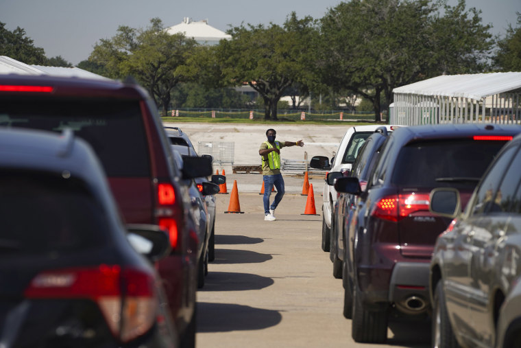 Image: An election worker guides voters in cars at a drive-through mail ballot drop-off site at NRG Stadium on Oct. 7, 2020 in Houston, Texas.