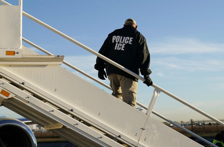An officer watches as immigrants are deported on a flight to El Salvador by U.S. Immigration and Customs Enforcement out of Houston in 2018.
