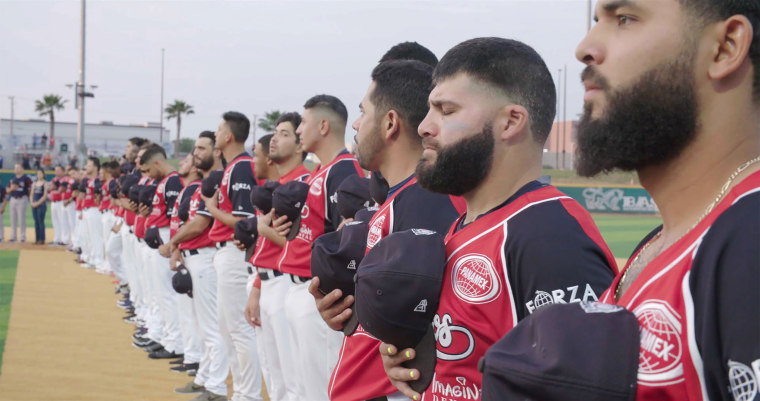 """Members of the Tecolotes de los Dos Laredo, a binational professional baseball team with home stadiums in Nuevo Laredo, Mexico, and Laredo, Texas, stand for the U.S. National Anthem in a scene from the Showtime documentary """"Bad Hombres."""""""