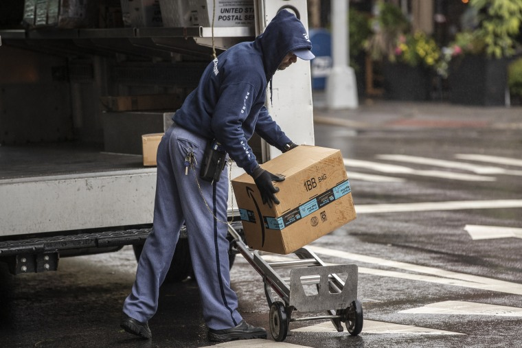 A USPS worker delivers Amazon packages in New York on Oct. 13, 2020.