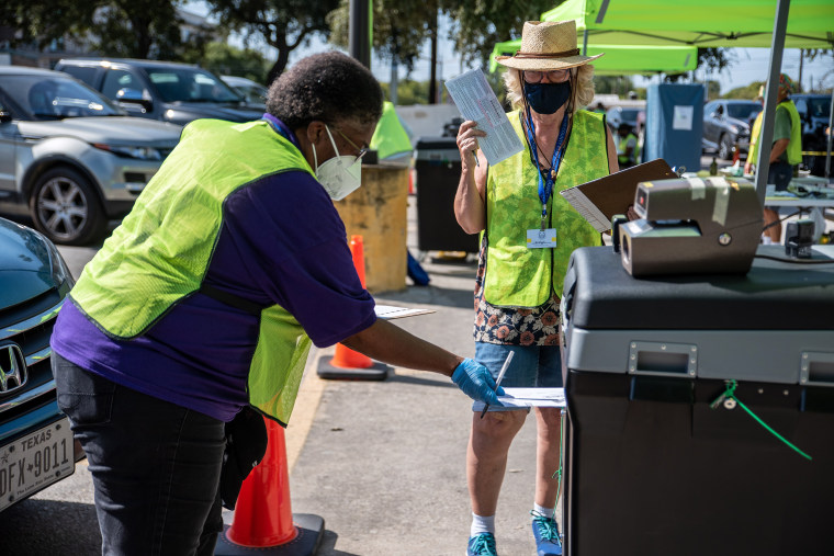Image: Workers drop voters ballots into a secure box at a ballot drop off location on Oct. 13, 2020 in Austin, Texas.