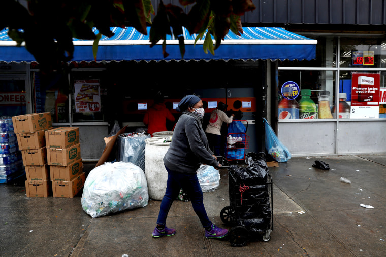 Image: A woman wearing a protective face mask pushes a cart by a recycling center as the spread of coronavirus disease (COVID-19) continues in the borough of Brooklyn in New York