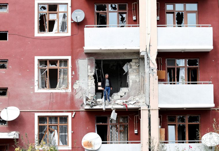 Image: A man looks out from his damaged home after a ceasefire begins during the fighting over the breakaway region of Nagorno-Karabakh in the city of Terter