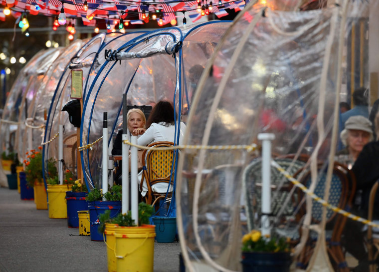 Diners eat outdoors in plastic tents at a restaurant in New York on Oct. 15, 2020.