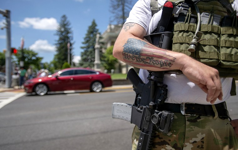 Second Amendment advocate Justin Hall of Roanoke stands guard with his firearm near the Smyth County Courthouse in Marion, Va., and its nearby Confederate statue on July 3.