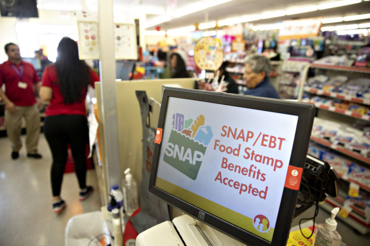 """Image: """"SNAP/EBT Food Stamp Benefits Accepted"""" is displayed on a screen inside a Family Dollar Stores Inc. store in Chicago, Illinois."""