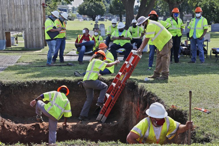 Workers climb out of the excavation site as work continues on a potential unmarked mass grave from the 1921 Tulsa Race Massacre at Oaklawn Cemetery in Tulsa, Okla., on July 14, 2020.