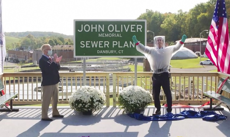 """John Oliver, host of """"Last Week Tonight with John Oliver,"""" right, with Mayor Mark Boughton during a dedication ceremony for The John Oliver Memorial Sewer Plant, in Danbury, Conn. Oliver made a secret trip to Connecticut last week to help cut the ribbon on a sign naming a sewage treatment plant in his honor."""