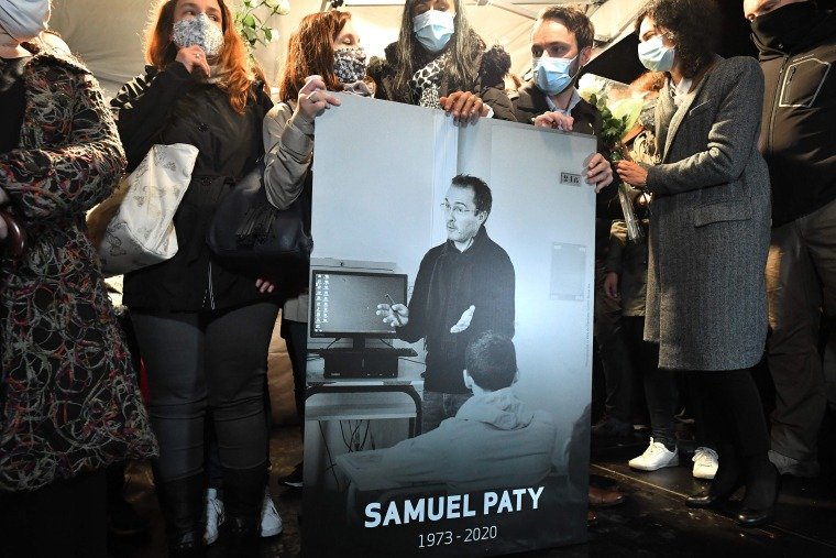 Image: Relatives and colleagues hold a picture of Samuel Paty during the 'Marche Blanche' in Conflans-Sainte-Honorine, northwest of Paris