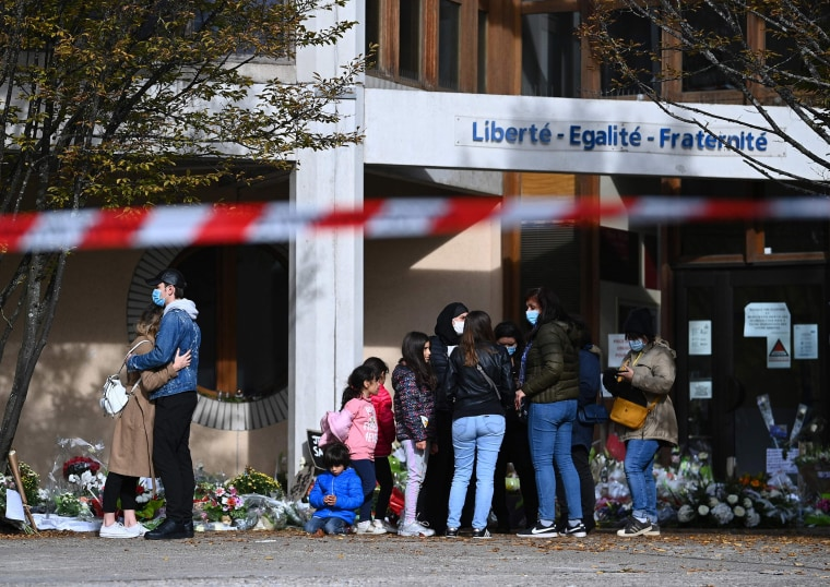 Image: People gather near flowers laid outside the Bois d'Aulne secondary school in homage to slain history teacher Samuel Paty