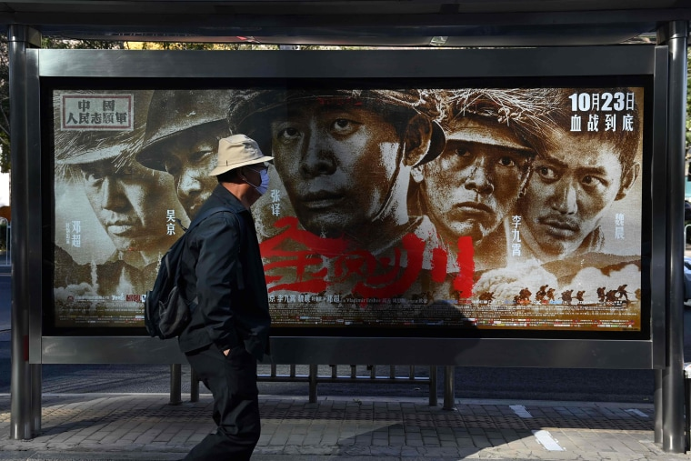 """Image: A man walks past a poster for the movie \""""Sacrifice\"""", about China's entry into the 1950-1953 Korean War to fight alongside North Korea against the U.S., in Beijing"""