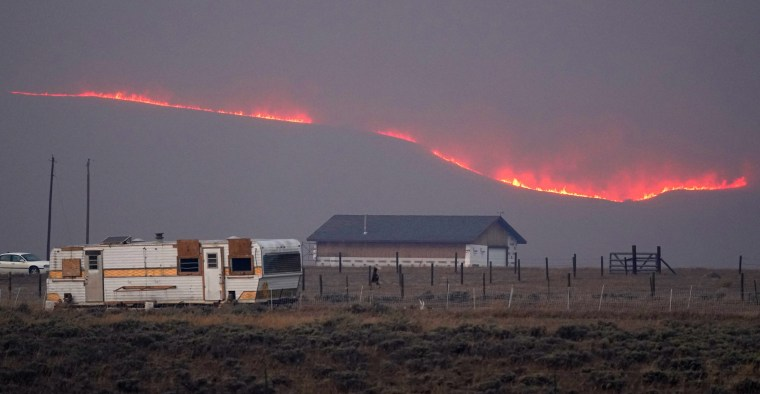 Flames rise from mountain ridges on Oct. 22, 2020, near Granby, Colo.