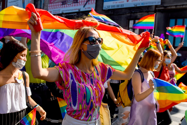 A supporter wears a protective face mask and holds a rainbow