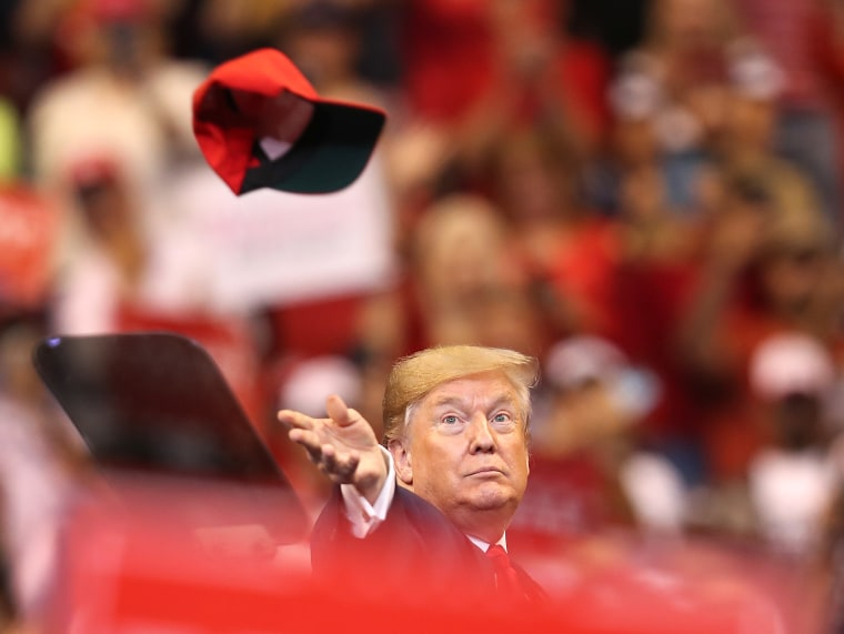 Image: U.S. President Donald Trump tosses a hat into the crowd