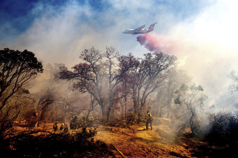 An air tanker drops retardant on the Olinda Fire burning in Anderson, Calif., on Sunday as high winds buffeted Northern California.