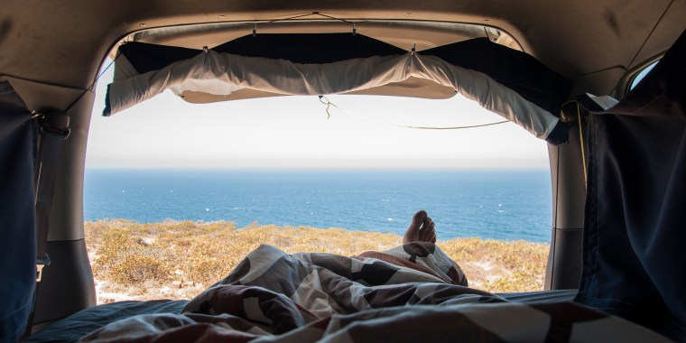 Person Sleeping In Van By Sea Against Sky