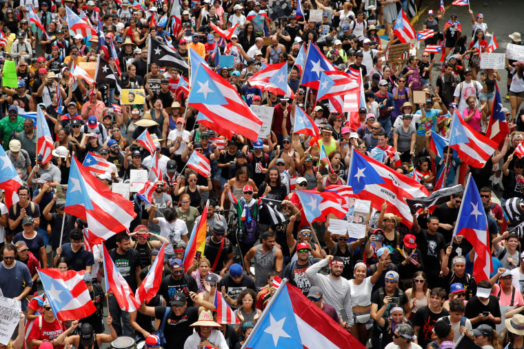 People wave Puerto Rican flags as they attend a rally to celebrate the resignation of Puerto Rican Governor Ricardo Rossello in San Juan