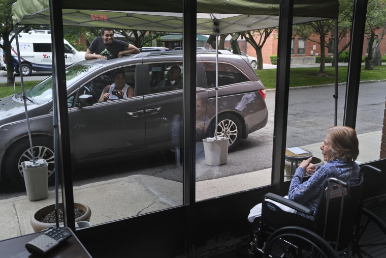 Gloria DeSoto, 92, visits with her family in their car through a window of the Hebrew Home at Riverdale in Bronx, N.Y., on June 11.
