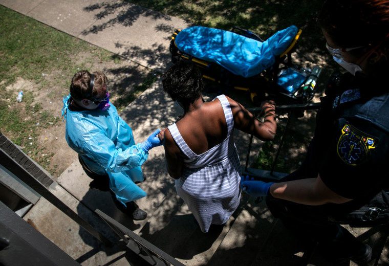 Image: Medics with Austin-Travis County EMS help a woman with Covid symptoms to a hospital in Texas on Aug. 4, 2020.