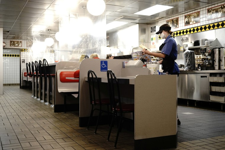 Image: A waitress works inside a Waffle House restaurant outfitted with plastic dividers amidst the coronavirus disease (COVID-19) in Findlay, Ohio.