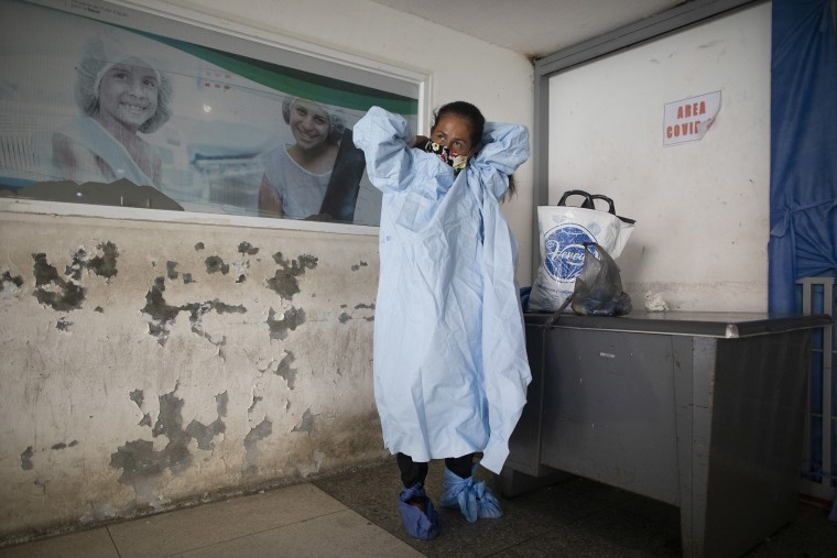 Image: Elena Suazo, a kindergarten cafeteria worker, puts on the protective gear she brought from home, outside the entrance to the COVID-19 wing of Jos? Gregorio Hern?ndez Hospital which used to be the emergency room