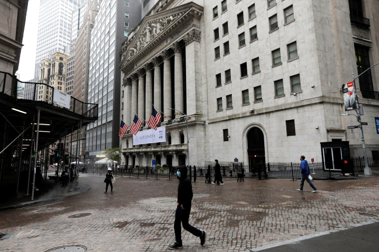Image: People wearing protective face masks walk outside New York Stock Exchange in New York