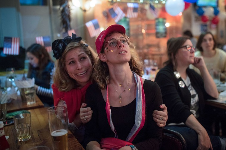 Democratic Party supporters react as they watch election results come in at the Democrats Abroad election night party at Marylebone Sports Bar and Grill, London