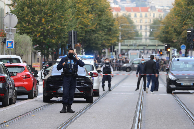 Image: French policemen stand guard a street after a knife attack in Nice, France