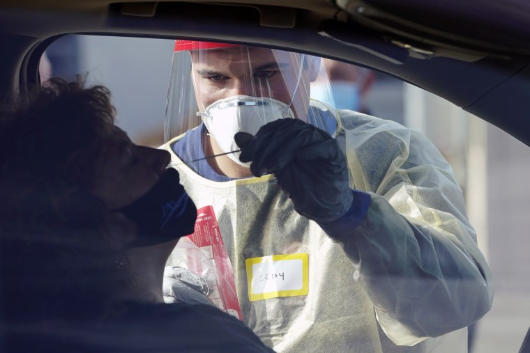 Cody Tupen, a firefighter with the Puget Sound Regional Fire Authority, performs a nose swab Covid-19 test on Nancy Backus, the mayor of Auburn, Wash., at a Covid-19 testing site Wednesday in Auburn, south of Seattle.