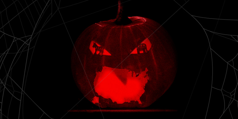 Image: A lit up carved pumpkin with a US shaped mouth and GOP and Democrat symbol shaped eyes.