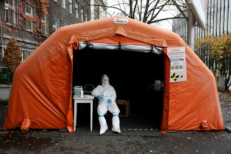 Image: A health worker in protective suit waits for people at a test center in Warsaw