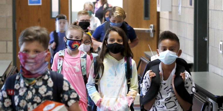 Wearing masks to prevent the spread of COVID-19, elementary school students walk to classes to begin their school day in Godley, Texas, on Aug. 5, 2020.