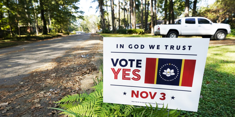 """A yard sign calling for support for the """"In God We Trust"""" flag."""