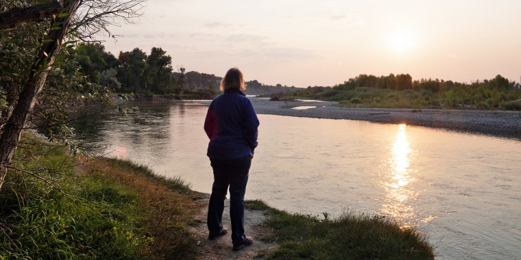 Overweight Woman Standing on a Riverbank at Sunrise